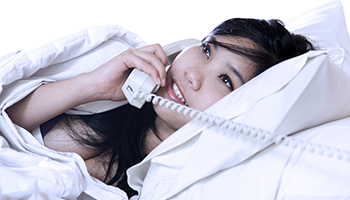 pretty asian girl on the phone in bed